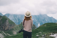 Young woman relaxing outdoor travel freedom lifestyle with mount. Ains on background. Fashionable girl in the Mangart is a mountain in the Julian Alps, located Royalty Free Stock Photography