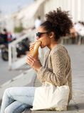 Young woman relaxing outdoors and eating food Royalty Free Stock Photography