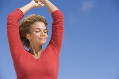 Young woman relaxing outside. Against blue sky Stock Image