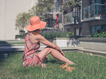 Young woman relaxing outside apartment block Stock Photo