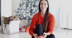 Young woman relaxing over the Christmas season. Pretty trendy young woman relaxing over the Christmas season sitting on the floor in the living room in front of stock video footage