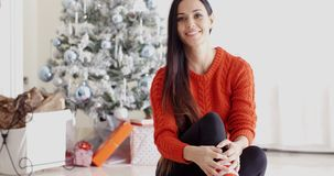 Young woman relaxing over the Christmas season. Pretty trendy young woman relaxing over the Christmas season sitting on the floor in the living room in front of stock footage
