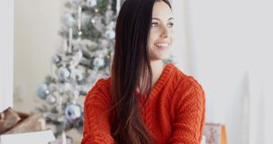 Young woman relaxing over the Christmas season. Pretty trendy young woman relaxing over the Christmas season sitting on the floor in the living room in front of stock video