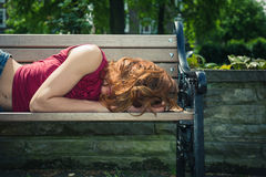 Young woman relaxing on park bench Stock Photos