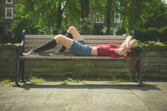 Young woman relaxing on park bench Stock Photography