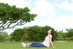 Woman enjoy the sun. Young woman relaxing at the park Stock Photo