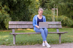 Young woman relaxing in a park using a laptop Stock Photos