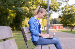 Young woman relaxing in a park using a laptop Stock Photo