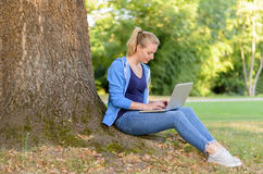 Young woman relaxing in a park using a laptop Royalty Free Stock Photo