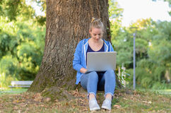 Young woman relaxing in a park using a laptop. Young woman in jeans and sneakers relaxing under a tree in a park using a laptop computer on her lap Royalty Free Stock Photography