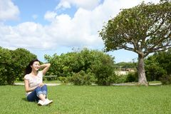 Woman enjoy the sun. Young woman relaxing at the park Royalty Free Stock Images