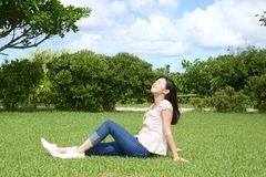 Woman enjoy the sun. Young woman relaxing at the park Stock Photography