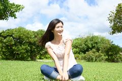Woman enjoy the sun. Young woman relaxing at the park Stock Image