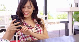 Young woman relaxing on a patio with a mobile stock video footage