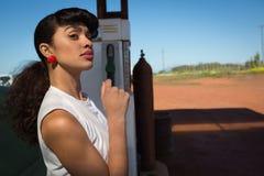 Woman relaxing at petrol pump station. Young woman relaxing at petrol pump station royalty free stock photos
