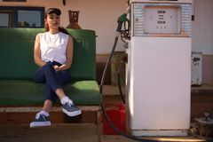 Woman relaxing at petrol pump station. Young woman relaxing at petrol pump station Royalty Free Stock Photography