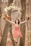 Young woman relaxing playing with leaves in autumn park Stock Photo