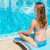Young woman relaxing on the pool Stock Photo