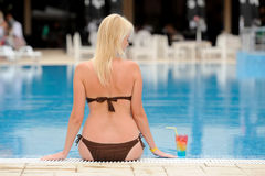 Young woman relaxing at the pool with cocktail Royalty Free Stock Image