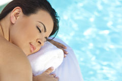 Young Woman Relaxing By Pool At Health Spa. Portrait of a beautiful young Latina Hispanic woman eyes closed laying down and relaxing by a swimming pool at a Royalty Free Stock Image
