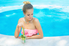 Young woman relaxing the pool with lemonade Stock Photo