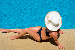 Young woman relaxing by the pool Royalty Free Stock Image