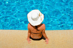 Young woman relaxing by the pool Stock Image