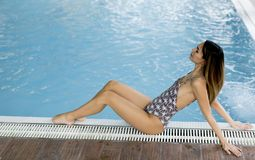 Young woman relaxing by pool side. In spa center Stock Image