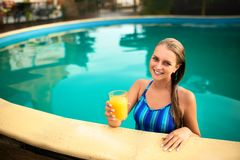 Young woman relaxing in a pool in summer with glass of orange juice. Pretty caucasian blonde girl wearing blue swimsuit stock photo