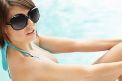 Young woman relaxing by the pool with sunglasses Stock Photo