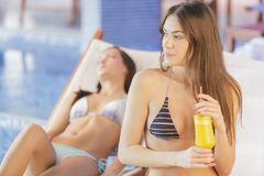 Young woman relaxing by the pool Stock Images