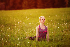 Young woman in a relaxing pose at the evening meadow Royalty Free Stock Image