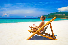Young woman relaxing in pose yoga on a beautiful beach. Royalty Free Stock Photo