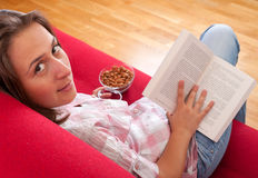 Young woman relaxing and reading a book Stock Photography