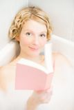 Young woman relaxing and reading a book in the bath Royalty Free Stock Photos
