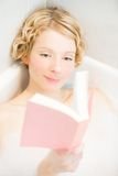 Young woman relaxing and reading a book in the bath Stock Photography
