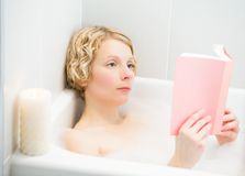 Young woman relaxing and reading a book in the bath Royalty Free Stock Images