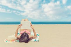 Young woman relaxing reading a book at the beach stock photo
