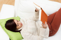 Young woman relaxing reading a book Stock Photography