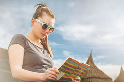 Young woman relaxing and reading a book on sunny day. On the beach in her leisure time as  summer recreation concept Stock Image
