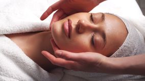 Beautiful young woman relaxing female receiving facial body massage beauty spa. Young woman relaxing during rejuvenating facial massage in beauty center stock footage