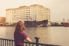 Young woman relaxing by river and looking across at buildings Royalty Free Stock Photos