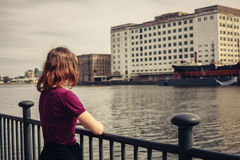 Young woman relaxing by river and looking across at buildings Stock Photo