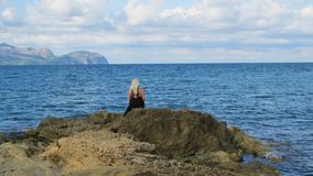 Young woman relaxing on the rock stock photo