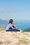 Young woman relaxing on a rock and enjoying the beauty of seascape sitiing on the mountain top. Travel, Healthy Royalty Free Stock Image