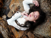 Young woman relaxing on the rocks Royalty Free Stock Photo