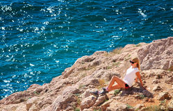 Young Woman relaxing on rocky cliff with blue Sea on background Stock Photo