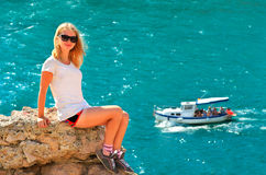 Young Woman relaxing on rocky cliff with blue Sea and Ship yacht on background Stock Photography