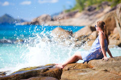 Young woman relaxing on rocky coast?. Young beautiful woman relaxing on rocky coast Royalty Free Stock Images