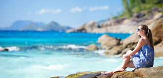 Young woman relaxing on rocky coast. Young beautiful woman relaxing on rocky coast Stock Photo